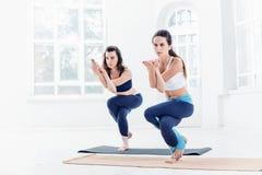 Lo studio ha sparato delle giovani donne che fanno gli esercizi di yoga su fondo bianco Immagine Stock Libera da Diritti