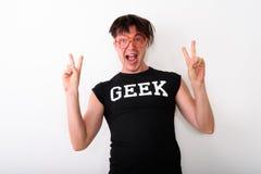 Lo studio ha sparato di giovane uomo felice del nerd che sorride mentre guardano ecciti fotografia stock libera da diritti