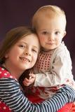 Lo studio ha sparato di un abbracciare delle due sorelle Fotografia Stock