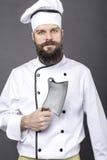 Lo studio ha sparato di un cuoco unico barbuto che tiene un coltello di macellaio Immagini Stock Libere da Diritti