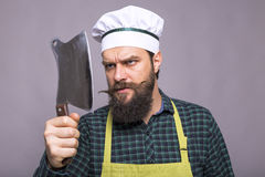 Lo studio ha sparato di un uomo barbuto arrabbiato che tiene un coltello di macellaio Fotografia Stock