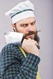 Lo studio ha sparato di un uomo barbuto arrabbiato che tiene un coltello di macellaio Fotografia Stock Libera da Diritti