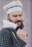 Lo studio ha sparato di un uomo barbuto felice che tiene un coltello di macellaio Fotografie Stock Libere da Diritti