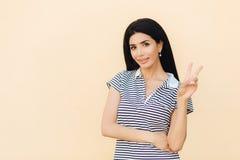 Lo studio sparato della femmina castana attraente con l'espressione contentissima, gesti dell'interno e segno di pace di manifest immagini stock libere da diritti