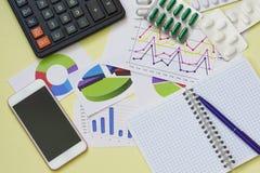 Lo studio sull'efficacia delle droghe Calcolatore, smartphone, blocco note e compresse sulla tavola immagine stock