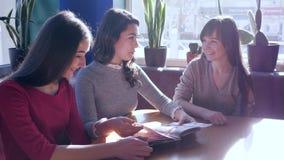 Lo svago allegro, società della donna sceglie l'alimento dal menu che si siede alla tavola in caffè archivi video
