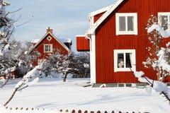 Lo svedese di legno rosso amily alloggia surronded da neve Fotografie Stock Libere da Diritti