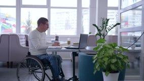 Lo sviluppo dell'uomo maturo disabile in sedia a rotelle nei vetri lavora al computer portatile durante la distanza online che im stock footage