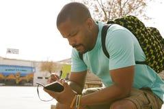 Lo zaino dell'uomo afroamericano attraente dei pantaloni a vita bassa e le note d'uso di fabbricazione in quaderno in città parch Fotografia Stock