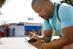 Lo zaino dell'uomo afroamericano pensieroso attraente dei pantaloni a vita bassa e le note d'uso di fabbricazione in quaderno in  Fotografia Stock Libera da Diritti