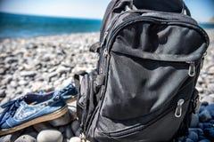 Lo zaino e le scarpe da tennis sono sulla spiaggia vicino al mare hanno lasciato il turista fotografie stock libere da diritti