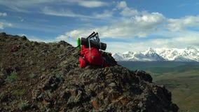 Lo zaino rosso del viaggiatore si trova sulla roccia Bastoni per seguire Ci sono i termos video d archivio
