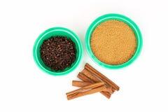 Lo zucchero bruno ed i chiodi di garofano organici in articoli verdi di festa lancia con cannella su bianco fotografia stock libera da diritti