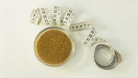 Lo zucchero bruno in un piccolo vetro trasparente urla e un nastro di misurazione arricciato nei centimetri accanto contro un fon immagini stock libere da diritti