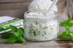 Lo zucchero casalingo sfrega con olio vegetale, le foglie di menta tagliate e l'olio essenziale della menta Fotografie Stock