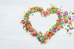 Lo zucchero colorato spruzza nella forma del cuore sulla tavola di legno bianca fotografia stock
