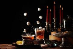 Lo zucchero cuba la caduta nei tazza da the di vetro su una regolazione rustica della tavola con le candele e le caramelle, dolce Fotografia Stock