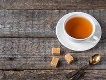 Lo zucchero di canna marrone bianco della tazza e del piattino di tè su un fondo di legno rustico copia lo spazio Immagini Stock Libere da Diritti