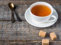 Lo zucchero di canna marrone bianco della tazza e del piattino di tè su un fondo di legno rustico copia lo spazio Immagine Stock