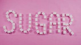 Lo zucchero di parola è presentato dai cubi dello zucchero raffinato su un fondo rosa Concetto della carie stock footage