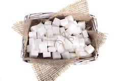 Lo zucchero raffinato di bianco è un mazzo in un canestro Fotografia Stock