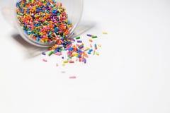 Lo zucchero variopinto spruzza su fondo bianco immagini stock