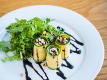 Lo zucchini rotola con il formaggio di mascarpone, i dadi, l'insalata verde e la salsa di soia Fotografie Stock