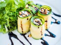 Lo zucchini rotola con il formaggio di mascarpone, i dadi, l'insalata verde e la salsa di soia Fotografie Stock Libere da Diritti