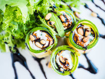 Lo zucchini rotola con il formaggio di mascarpone, i dadi, l'insalata verde e la salsa di soia Immagini Stock