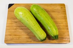 Lo zucchini verde fresco due pezzi si trova su un bordo di legno fotografie stock