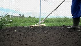 Loa angle shot of farmer using the rake shot in slow motion stock video footage
