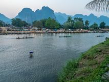 Loa man fishing on Nam Song River. Laotian fisherman collecting net for small fish while wading in the Nam Song River. Sun setting over impressive limestone Royalty Free Stock Photo