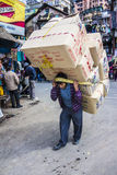 Load carrier in darjeeling. A load carrier carrying a heavy load in the streets of Darjeeling, India Stock Photos