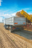 Loadding potato in tipper on harvested filed Stock Photo