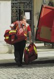 Loaded. Postman carrying several heavy delivery bags stock photography