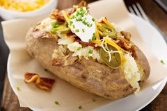 Loaded baked potato with bacon and cheese. Loaded baked potato with bacon, cheese sour cream and chives Stock Images