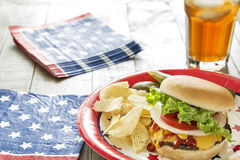 Loaded cheeseburger at a patriotic themed cookout. A cheeseburger is loaded with ketchup, mustard, onion, tomato and lettuce at a patriotic themed BBQ.  It is Stock Image