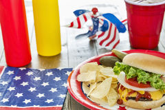 Loaded cheeseburger at a patriotic themed cookout. A cheeseburger is loaded with ketchup, mustard, onion, tomato and lettuce at a patriotic themed BBQ.  It is Royalty Free Stock Photos