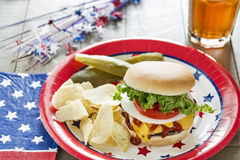 Loaded cheeseburger at a patriotic themed cookout Stock Images