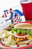 Loaded cheeseburger at a patriotic themed cookout. A cheeseburger is loaded with ketchup, mustard, tomato, onion and lettuce at a patriotic themed BBQ.  It is Royalty Free Stock Photography