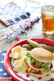 Loaded cheeseburger at a patriotic themed cookout. A cheeseburger is loaded with ketchup, mustard, tomato, onion and lettuce at a patriotic themed BBQ.  It is Royalty Free Stock Photos