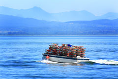 Loaded Crabbing Boat. A loaded crabbing boat with crab pots is a common sight in Puget Sound Washington with a forested hills, mountains and shoreline in the Stock Images