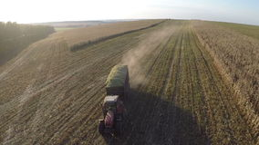 Loaded with crops tractor driving on field, aerial view. Flying over the tractor with trail full of harvested crops driving on farmland. Agriculture and stock video footage