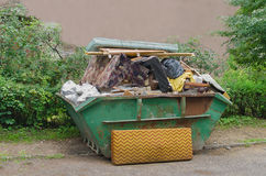 Loaded dumpster. Green container with household waste against the green wood Stock Photo