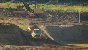 The loaded mining dump truck leaves the hill. On a sandy quarry stock video footage