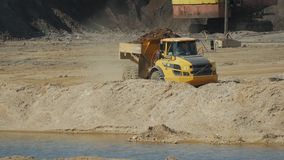 A loaded mining truck slowly moves along a quarry