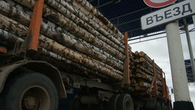 Loaded Red Truck with Trailers Drives Through Check Point. Closeup red truck with trailers loaded with logs leaves modern transit traffic check point against stock footage
