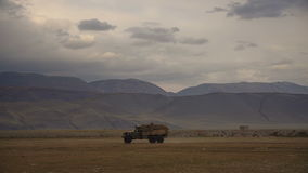 Loaded Truck Driving Across A Field With Hills And Mountains On The Background In Daytime Under Cloudy Sky. Autumn Landscape With A Vehicle Passing Through stock video