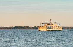 A vehicle ferry crosses open water at sunset stock images