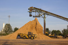 A Loader and Bark Mulch. A front end loader removes bark mulch from a large pile Royalty Free Stock Photography